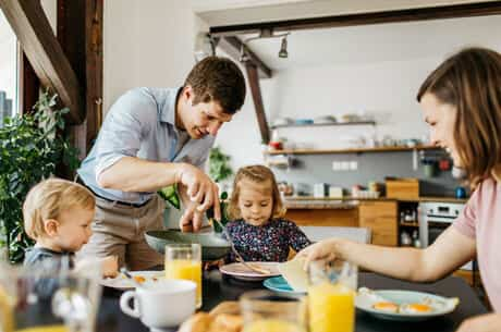 father serving family breakfast